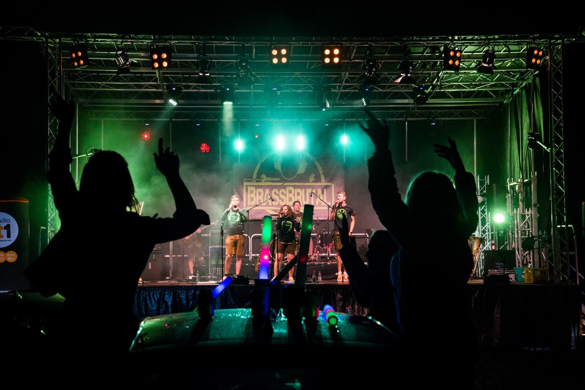 BrassBrutal live auf der Bühne beim Autokinokonzert. Menschen tanzen in den Autos.
